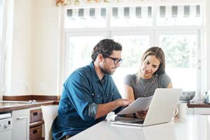 young couple working on their finances together at home