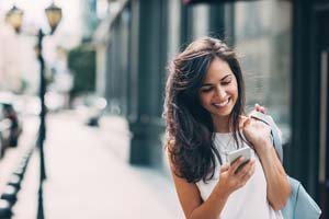 Smiling young woman walking outdoors at urban setting and checking messages.